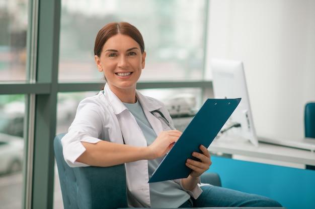 Een glimlachende vrouw in een wit gewaad die een lijst met recepten vasthoudt en er tevreden uitziet