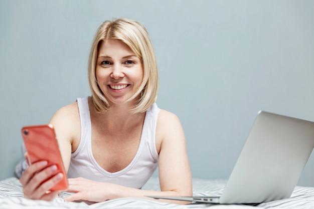 Een glimlachende vrouw in pyjama ligt op haar buik in bed met een laptop en een smartphone. bloggen en telewerken tijdens de coronavirus pandemie. quarantaine en zelfisolatiemodus.