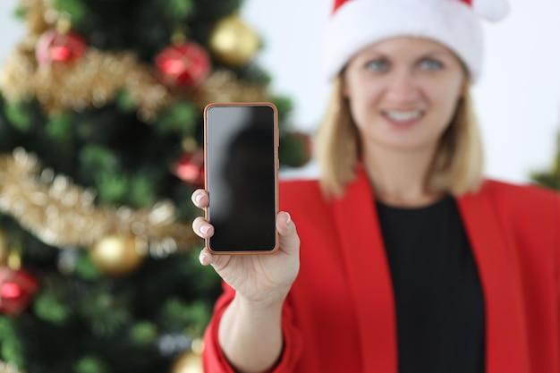 Een glimlachende vrouw met een kerstmuts houdt een smartphone vast op de achtergrond van de kerstboomverkoop van