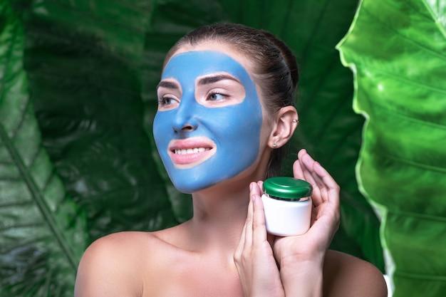 Een glimlachende vrouw met een masker van blauwe klei op haar gezicht houdt een potje room vast.