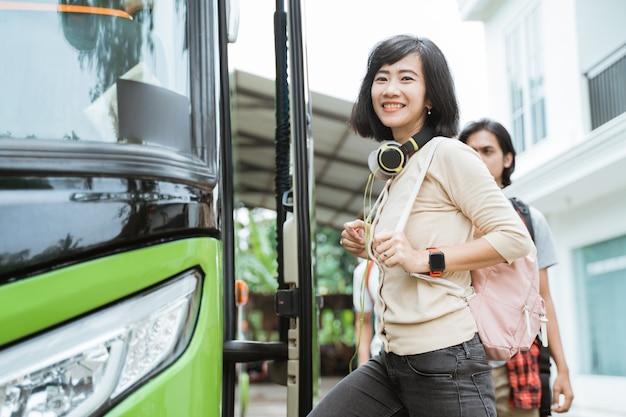 Een glimlachende vrouw met een rugzak en koptelefoon op weg naar de bus