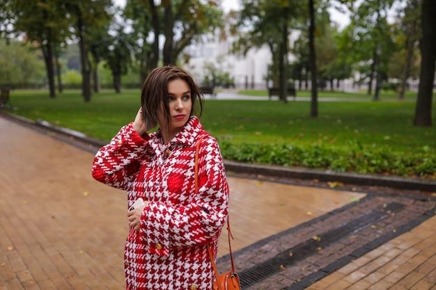 Een glimlachende vrouw van middelbare leeftijd die de herfstkleren draagt.