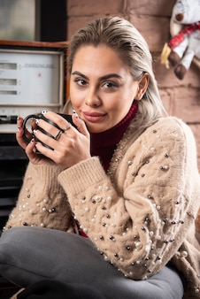 Een glimlachende vrouw zit en houdt een kopje koffie vast