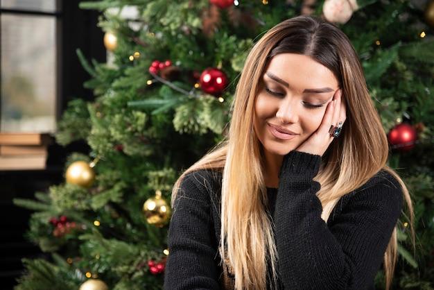 Een glimlachende vrouw zittend op een gezellige bank bedachtzaam. hoge kwaliteit foto