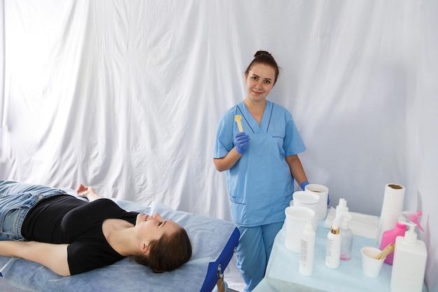 Een glimlachende vrouwelijke arts is een schoonheidsspecialiste naast een vrouw die op een massagetafel ligt