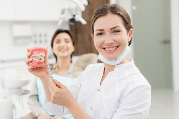 Een glimlachende vrouwelijke tandarts met kunstgebit in haar handen. bij de tandarts