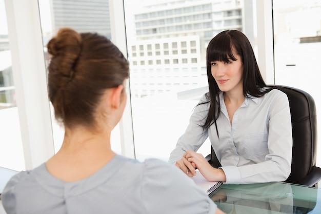 Een glimlachende zakenvrouw luistert naar wat de andere vrouw te zeggen heeft