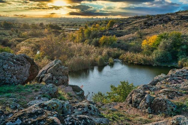 Een glimmend mooi riviertje tussen grote witte stenen en groene vegetatie op de heuvels in oekraïne