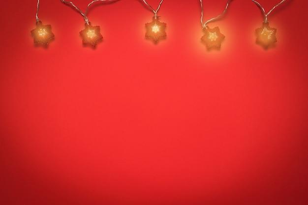 Een gloeiende slinger van vijf gloeilampen op een rode achtergrond.