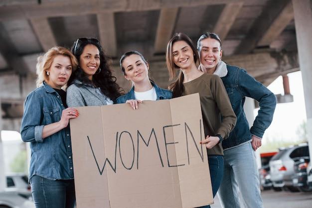 Een goed humeur hebben. een groep feministische vrouwen protesteert buitenshuis voor hun rechten