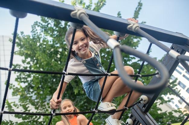 Een goede tijd hebben. meisjes hebben plezier in de klimrek en voelen zich genoten