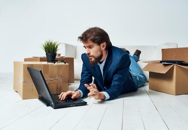 Een goedkope man ligt op de grond voor een laptopkantoor, wissel van werkplek