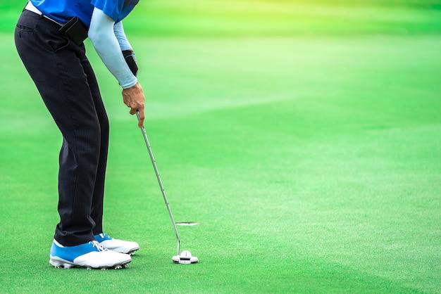 Een golfspeler zet een putter op de bal om het gat te raken om het doel te bereiken.