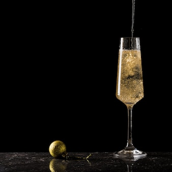 Een gouden bal en een glas gevuld met mousserende wijn op een zwarte achtergrond.