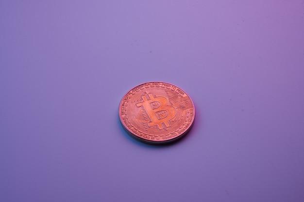 Een gouden bitcoin geïsoleerd op roze paarse achtergrond close-up met kopie ruimte
