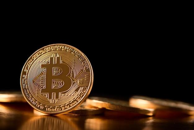 Een gouden bitcoin op de rand die wordt weergegeven op de achtergrond van andere cryptocurrencies die de toekomstige trend van virtueel geld introduceren.