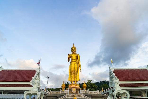 Een gouden boeddhabeeld met lucht op de bergtop in hat yai gemeente openbaar park, songkhla provincie, thailand