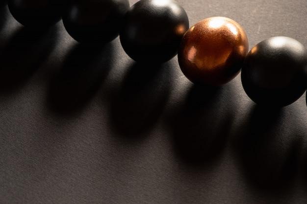 Een gouden ei en zwarte eieren liggen in een rij op zwarte achtergrond met kopie ruimte