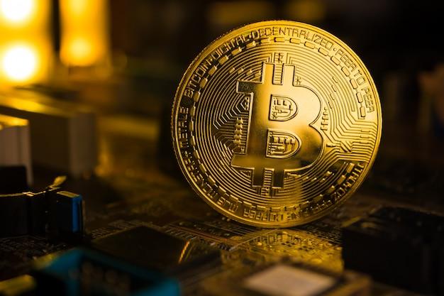 Een gouden munt met bitcoin symbool op een moederbord.