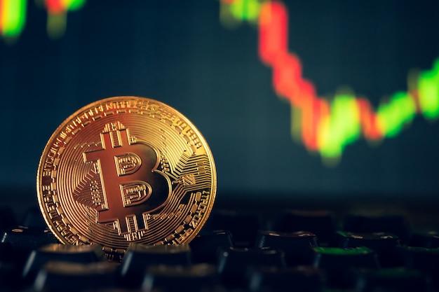 Een gouden munt met bitcoinsymbool op computertoetsenbord met de achtergrond van de voorraadgrafiek.