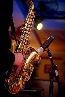 Een gouden saxofoon in de handen van een muzikant in de buurt van de microfoon op het aanrecht.