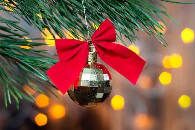 Een gouden speelgoeddiscobal met een rode strik hangt aan een tak van een kerstboom op een bokeh-achtergrond
