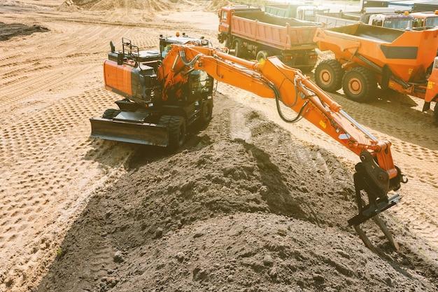 Een graafmachine op een bouwplaats plant de grond voordat hij aan de fundering gaat werken