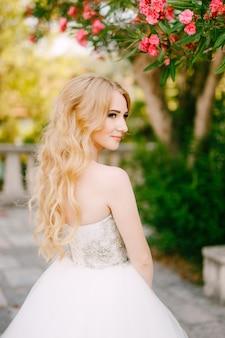Een gracieuze blonde bruid staat onder de takken van een bloeiende oleander in de buurt van de oude kerk in