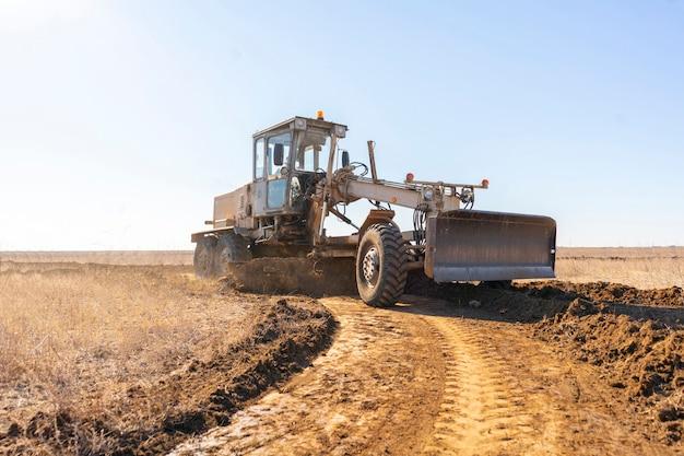 Een gradermachine die een nieuwe weg maakt, graaft het grind in het veld