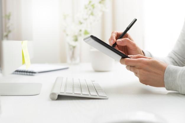 Een grafisch ontwerper tekent op een tablet.