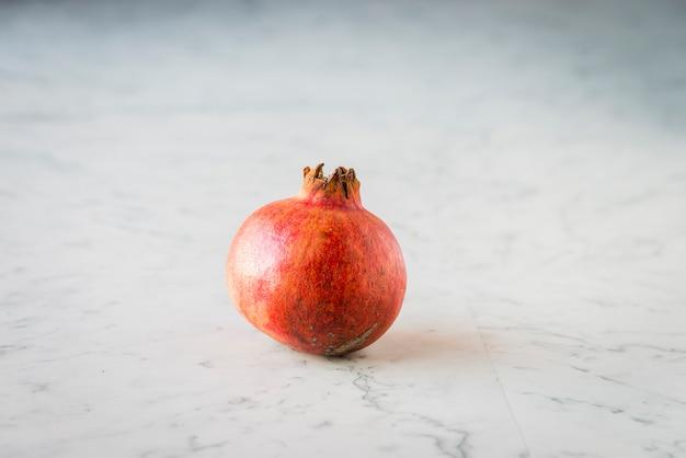 Een granaatappel alleen op een marmeren tafel