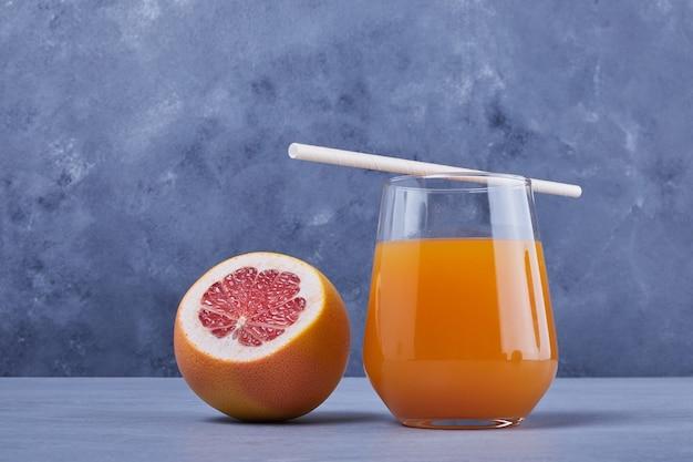 Een grapefruit met een glas sap.