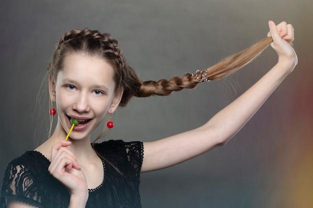 Een grappig en ondeugend tienermeisje met een lolly en een lange vlecht.
