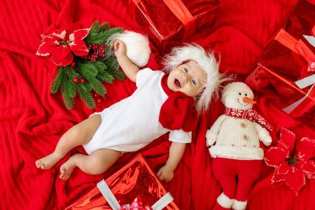 Een grappig kind in een kerstman kostuum ligt op een rode achtergrond tussen geschenken