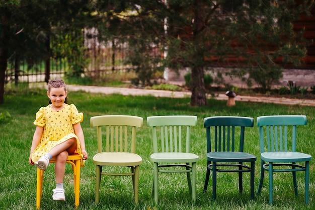 Een grappig meisje in een gele jurk zit op een rij stoelen die op het grasveld in het park staan en pr...