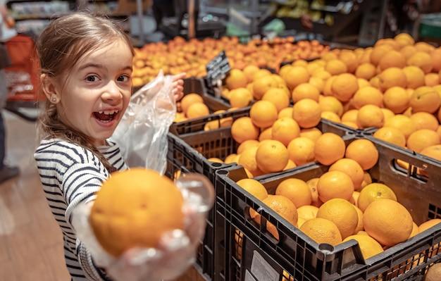 Een grappig meisje in een supermarkt kiest sinaasappels om te kopen.
