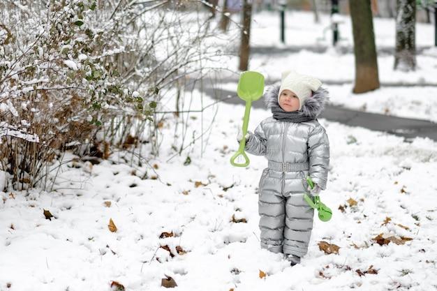 Een grappig meisje in een warme zilveren jumpsuit houdt een speelgoedschop vast. gelukkig kind op een winterse wandeling in het park.