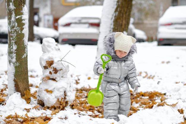 Een grappig meisje in een zilveren jumpsuit houdt een speelgoedschop vast en maakt een sneeuwpop