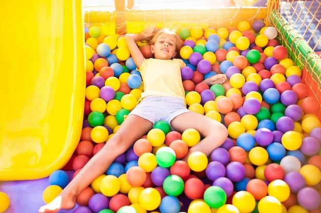 Een grappig meisje zit in een speeltuin met zachte en lichte apparatuur en gooit kleurrijke ballen naar de camera terwijl ze geniet van de warme zomerzon