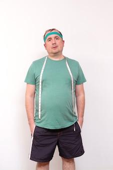 Een grappige dikke man in een groene bandana en een shirt met een meetlint om zijn nek thuis fitness training onafhankelijke training