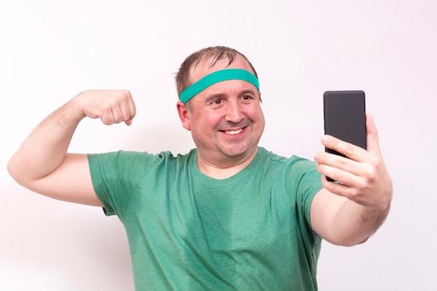 Een grappige dikke man in een groene bandana en t-shirts neemt een selfie van zijn rechter biceps thuis fitness training onafhankelijk afstandsonderwijs