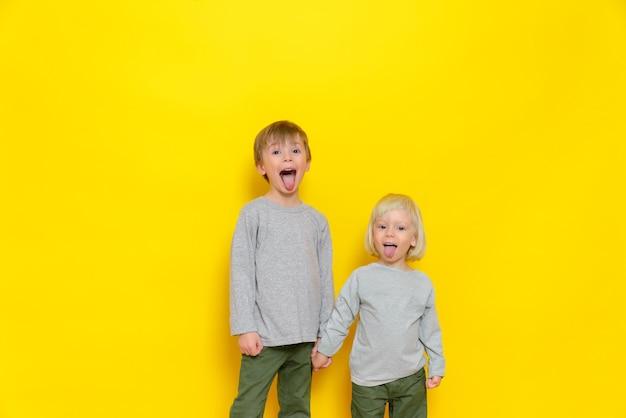 Een grappige jeugd van twee jongens die grijnzen en plagen en hun tong laten zien