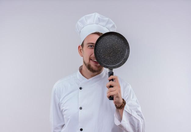 Een grappige jonge bebaarde chef-kok man met wit fornuis uniform en hoed met koekenpan voor zijn gezicht terwijl hij op een witte muur kijkt