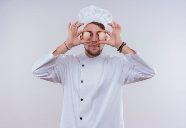 Een grappige jonge, bebaarde chef-kokmens die een wit fornuisuniform en een hoed draagt die organische eieren voor zijn ogen op een witte muur houdt