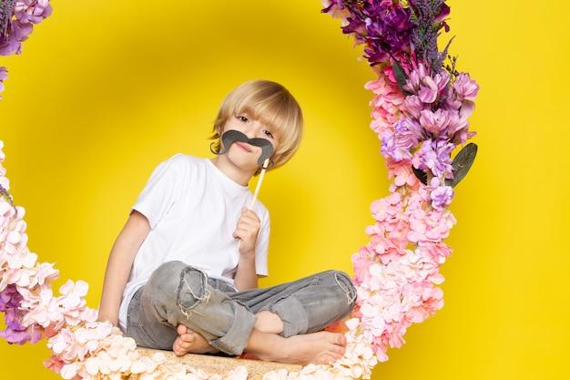 Een grappige jongen van het vooraanzichtblonde in de witte t-shirtholding snor op de gele vloer