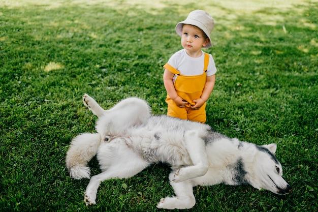 Een grappige kleine jongen poseren met de hond in de tuin