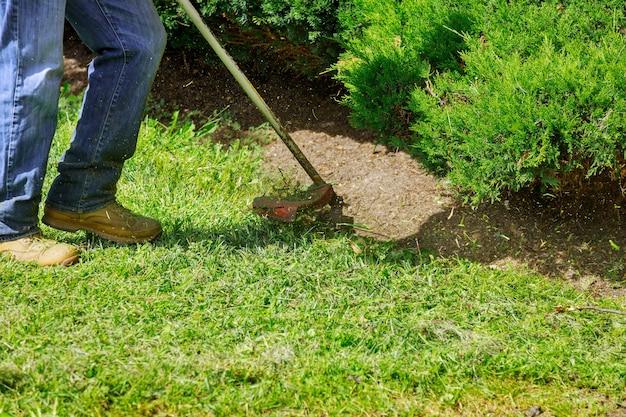 Een grasmaaier maait vers, groen gras op het gazon dichtbij, een gemeentelijke arbeider met grasmaaier in zijn hand.
