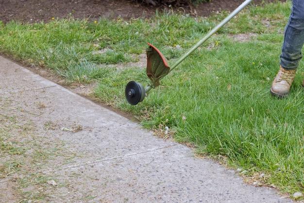 Een grasmaaier maait vers, groen gras op het gazon in de buurt, een gemeentewerker met grasmaaier