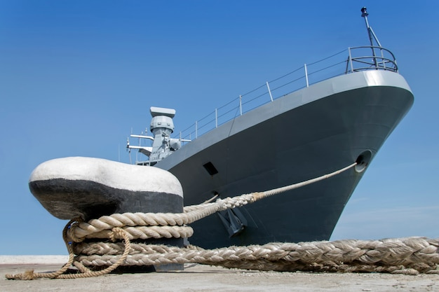 Een grijs modern oorlogsschip afgemeerd door touwen aan de kust.