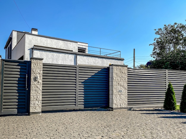 Een grijs privéhuis van twee verdiepingen verscholen achter een hek met automatische schuifbare bruine poorten en een gebied bij het huis tegen een blauwe lucht.